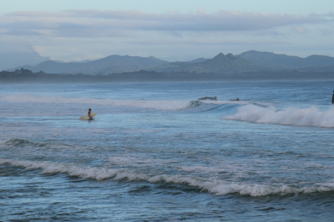 A lone surfer enters the water at Byron Bay in Australia.