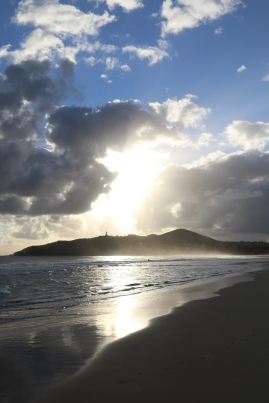 The sun streams through the clouds at Byron Bay in Australia.