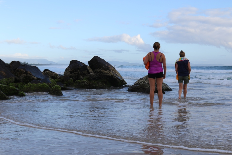 Two girls look out to sea from a beach at Byron Bay in Australia.