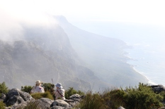Two ladies sit atop Table Mountain in Cape Town, South Africa taking in the views.